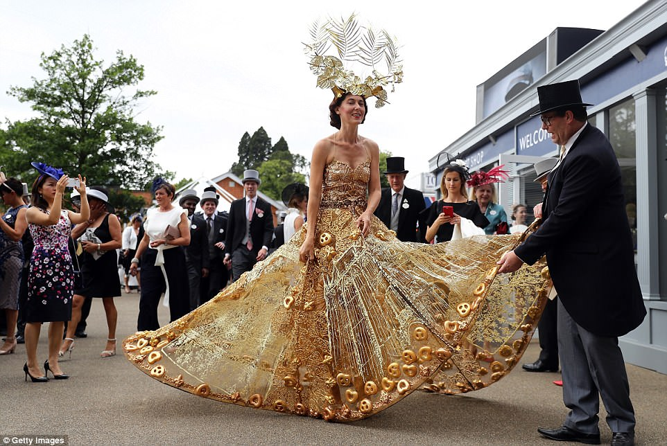 Go for gold! Designer Larisa Katz turned heads a gigantic metallic ballgown spanning almost three metres in diameter and topped with a leaf-shaped headpiece, as she joined a host of glamorous guests descending on Royal Ascot on Wednesday