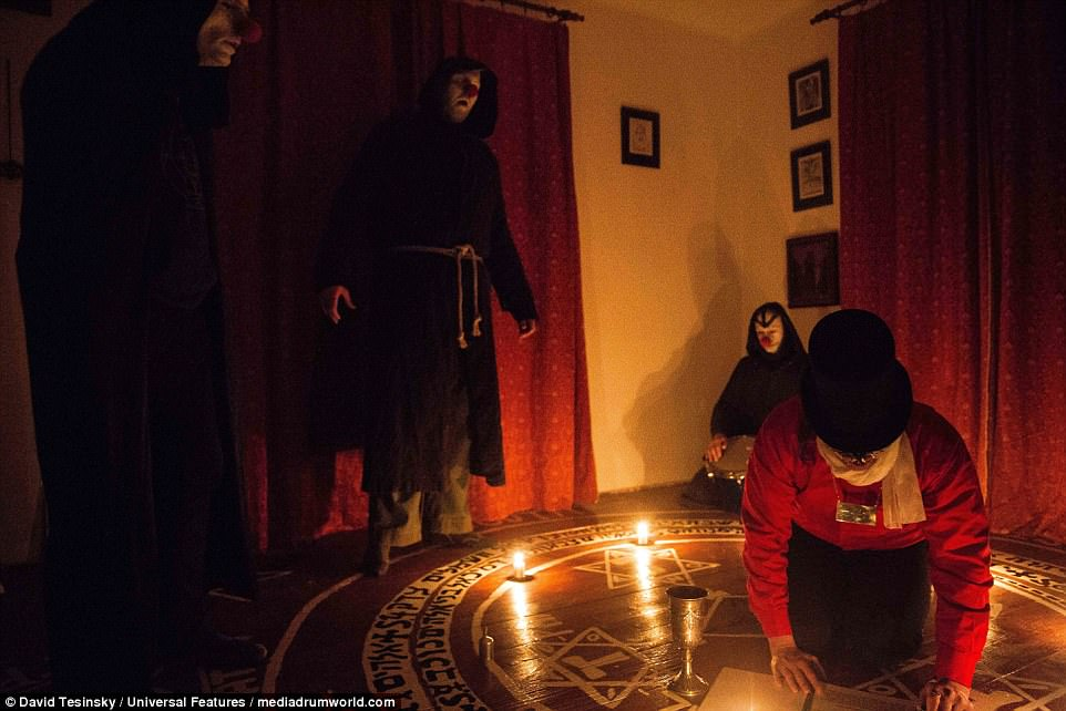 The group were believed to be taking part in a 'dark harlequin-style' ritual as they sit around a symbol drawn on the floor