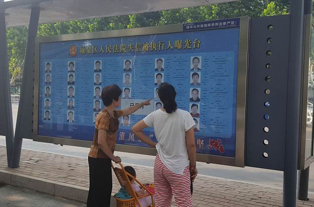 The 'wall of shame' was established by the Fuyang Yingquan People's Court court in Anhui province in June as part of a move to guilt borrowers who have failed to pay off debts