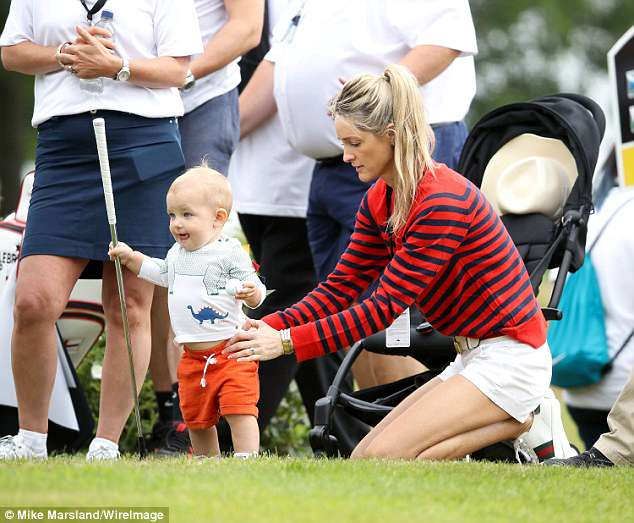 Soaking up the sun: Storm put on a leggy display in white denim shorts and a red striped jumper while little Cooper played with his dad's golf club
