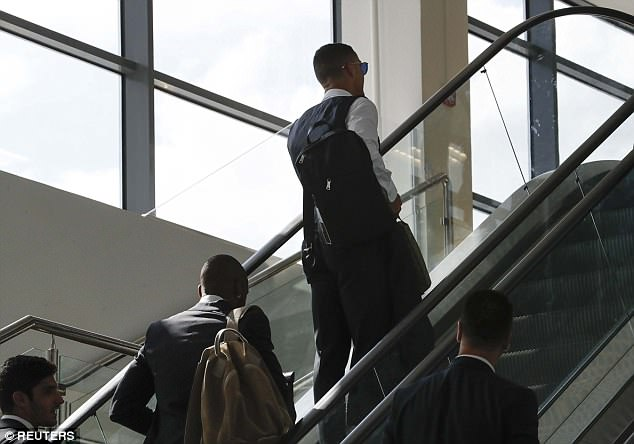 The 33-year-old makes his way up the escalators while his team-mates follow on behind