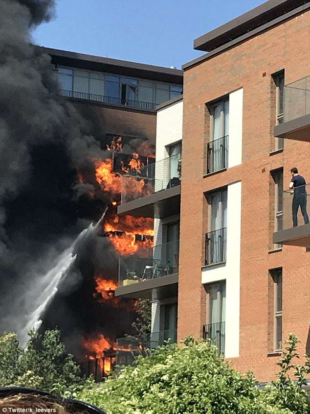 A residents of a nearby block of flats watches on as firefighters spray water onto the blaze which has engulfed four balconies