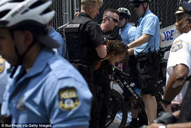 A woman screams in agony as several officers place her under arrest during the protests
