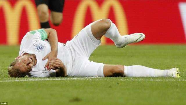 England captain Harry Kane clutches his chest after being brought down in the centre circle attempting to launch a counter