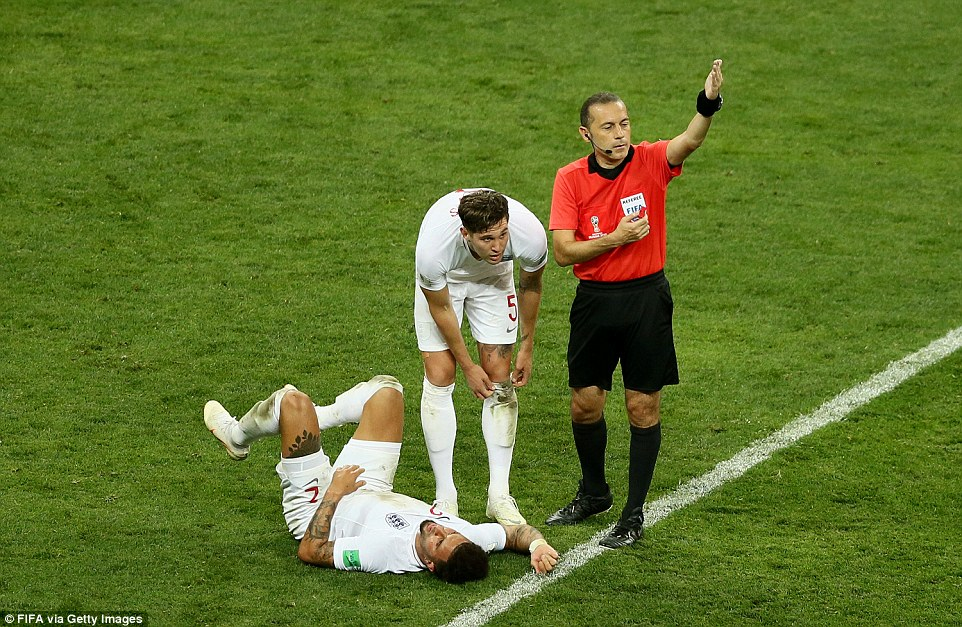 The referee calls for medical attention to be given to Walker after the ball struck him in the midriff from a fierce shot at goal