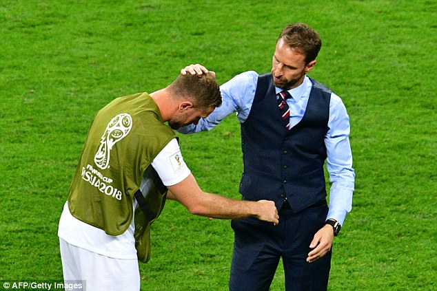 The midfielder is commiserated by the England manager following the defeat in Moscow