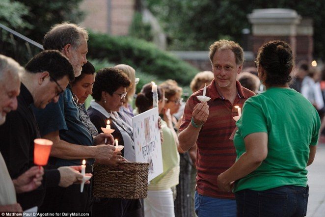 Michael Beer, from Nonviolence International, (second from right), attends the silent protest where attendees held candles and held signs demonstrating against the child and family detentions