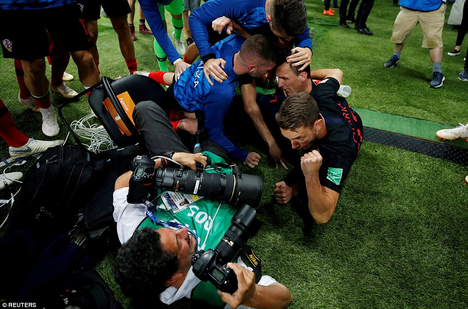How he did it:  Agence France-Presse photographer Yuri Cortez unwittingly became part of the celebrations as he was buried under a pile of joyous players - but kept taking photos