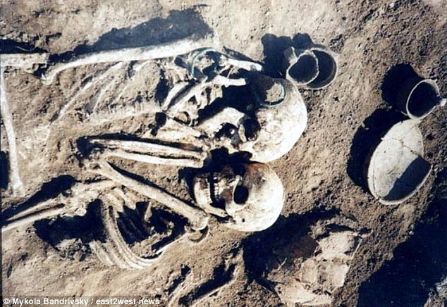They were discovered entwined in the grave alongside a number of pots and pans near their heads