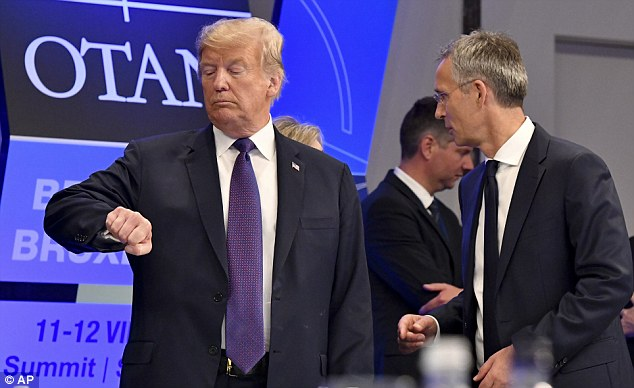 TIME FOR ME TO FLY: President Donald Trump checks the time as NATO Secretary General Jens Stoltenberg stands beside him, at the Art and History Museum at the Park Cinquantenaire in Brussels on Wednesday, July 11, 2018