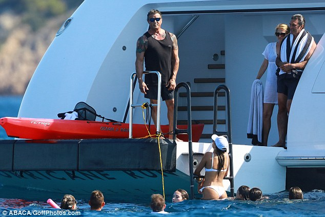 Leading man! The action man stood tall as he chatted to his brood and friends from the yacht