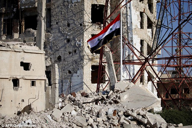 The Syrian national flag rises in the midst of damaged buildings in Daraa-al-Balad, an opposition-held part of the southern  city of Daraa, today (July 12)