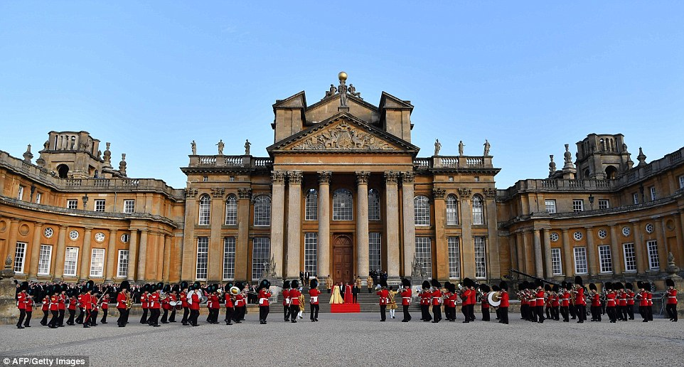US First Lady Melania Trump, US President Donald Trump, Britain's Prime Minister Theresa May and her husband Philip May stand on steps in the Great Court watching and listening to the bands of the Scots, Irish and Welsh Guards perform a ceremonial welcome
