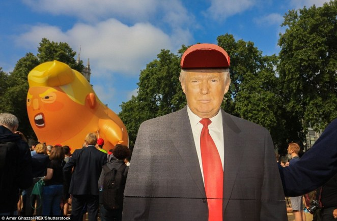"""A few hundred people gathered to watch the blimp launch in Parliament Square, with organisers of the stunt wearing red boiler suits and red baseball caps emblazoned with """"TRUMP BABYSITTER"""""""