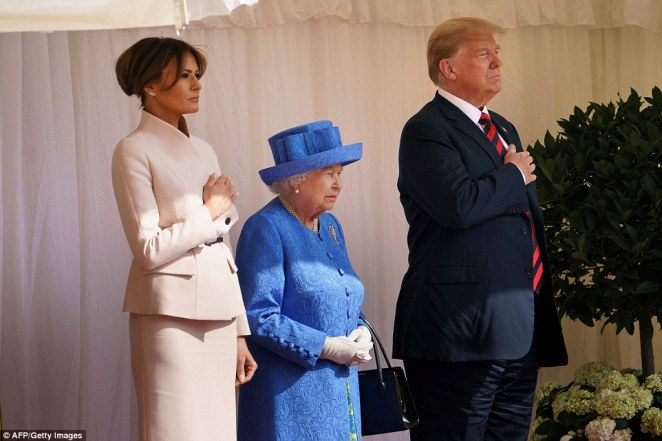 The President and First Lady stand with their hands on their hearts as they are treated to a performance of the US national anthem at the castle