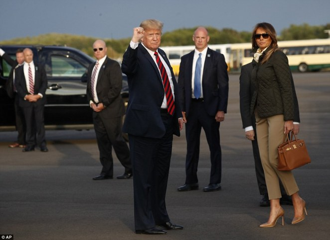 President Donald Trump and first lady Melania Trump look at the media assembled for their arrival on Air Force One at Glasgow Prestwick Airport