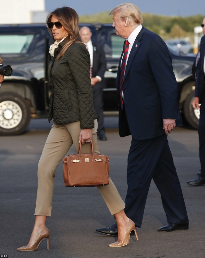 Showing it off: Melania flaunted her pricey Hermes Birkin as she and Trump made their way into a waiting SUV, which will presumably transport them to the family's golf course at Turnberry, where the first couple will spend the weekend