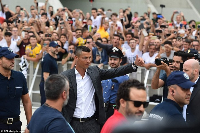 Cristiano Ronaldo greets excited Juventus fans as he arrives at the Allianz Stadium for his medical and to complete his move