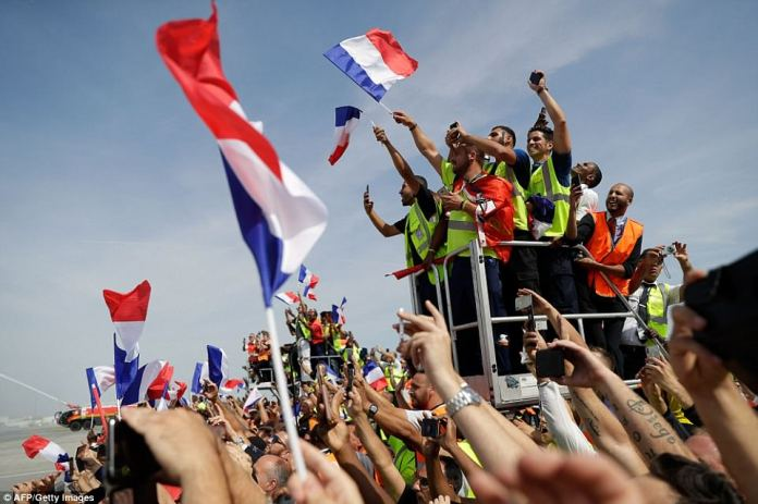 France's fans wave French national flags as they wait for the arrival of France's national football team at the Roissy-Charles de Gaulle airport on the outskirts of Paris