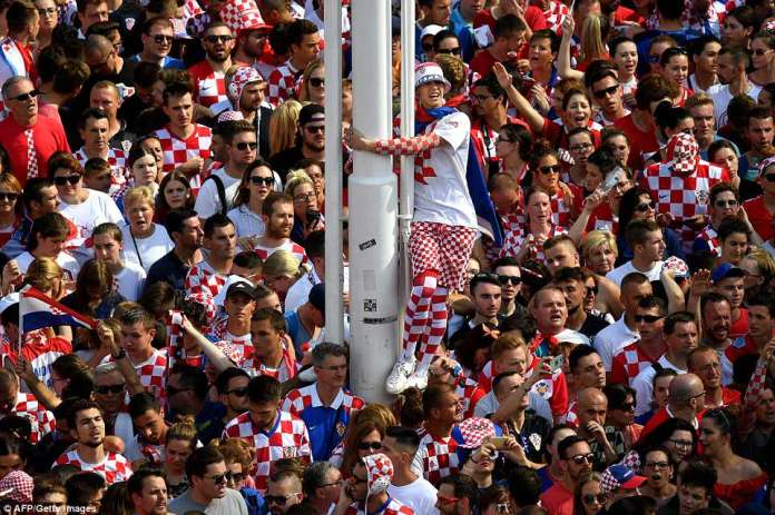 One fan climbed up the side of a pole to get a better view of the team among a sea of red and white chequered shirts