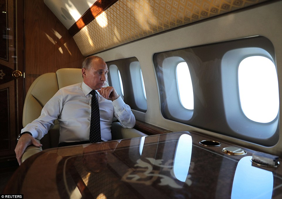 Putin relaxes on one of his planes in December 2017 as he travels to theHmeymim air base in Syria