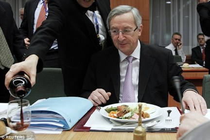 An aide pours out a glass of red forJuncker as he attends an European finance ministers meeting in Brussels in 2011