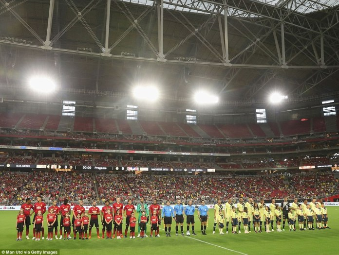 The Manchester United team line up next to their opponents at University of Phoenix Stadium