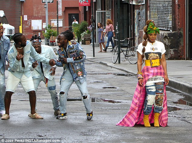Street cred: Her dancers were dressed in blue denim and sneakers and they put on their moves as they followed her down the street while cameras rolled