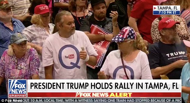 Followers of the online conspiracy were seen in the audience at President Trump's Tampa rally
