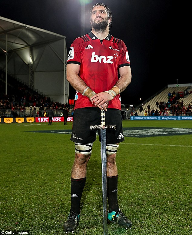 Sam Whitelock (C) captain of the Crusaders celebrates with a sword on the pitch