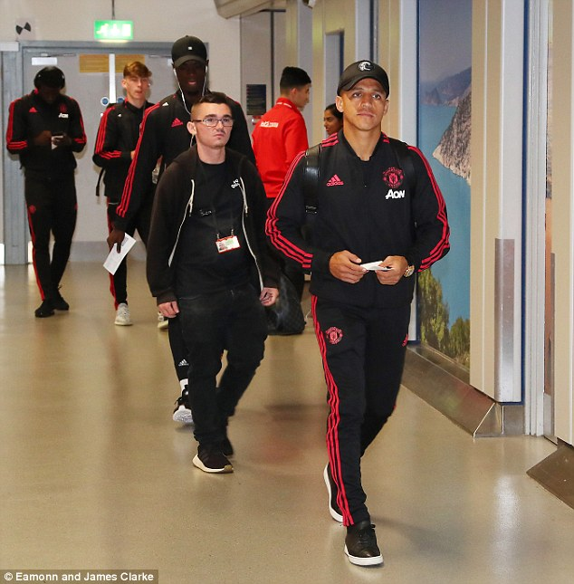 Alexis Sanchez makes his way into the airport ahead of their flight to Munich early on Sunday
