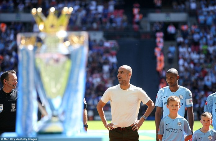 City manager Guardiola lines up alongside his players and in front of the Premier League trophy ahead of kick-off