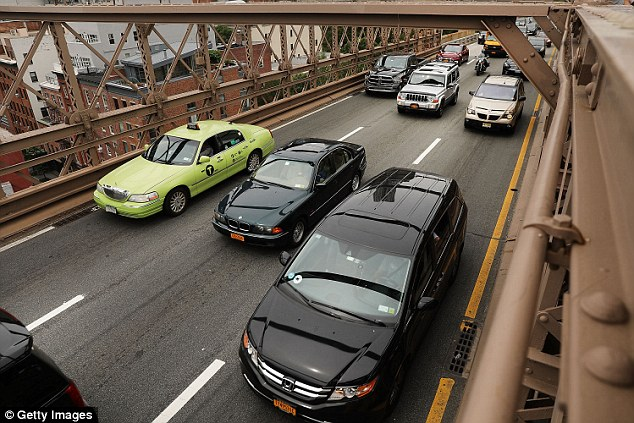New York City moved Wednesday to regulate the explosive growth of Uber and other app-based ride services with a temporary cap on new licenses for ride-hailing services. Cars are seen above driving on the Brooklyn Bridge last week