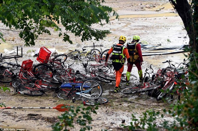 Rescuers walk past damaged bicycles on a flooded campsite in southern France as storms and heavy rain sweep the country