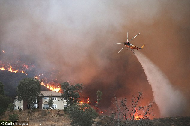 A US Air Force officer has proposed dropping bombs to put out wildfire flames. Pictured: A firefighting helicopter makes a water drop as the Holy Fire burns near homes in Lake Elsinore, California