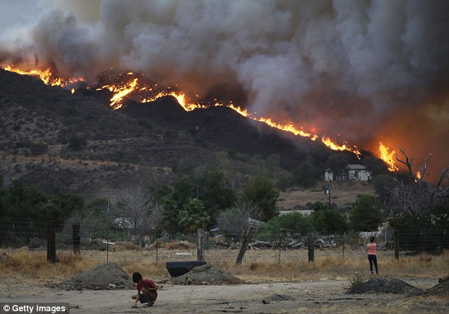 The fire continues to grow amidst a heat wave and has now burned 10,236 acres while remaining just five percent contained. Pictured: Lake Elsinore on Thursday