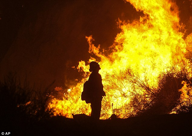 A firefighter keeps watch as the Holy Fire burns in the Cleveland National Forest along a hillside at Temescal Valley in Corona, Calif., Thursday, Aug. 9, 2018