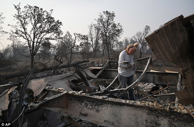 Alyson Kohl wipes her face as she combs through the charred remains of her home burned in the Carr Fire, Saturday, Aug. 11, 2018, in Redding, Calif.