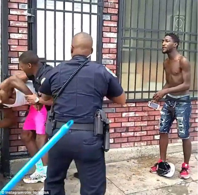 The officer grabs McGrier by the arm and takes him down to the pavement near his partner