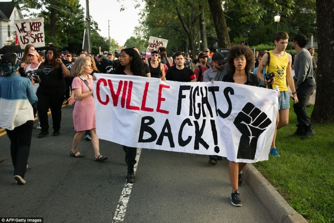 Demonstrators march down Rugby Avenue near the University of Virginia campus one year after the Unite the Right rally