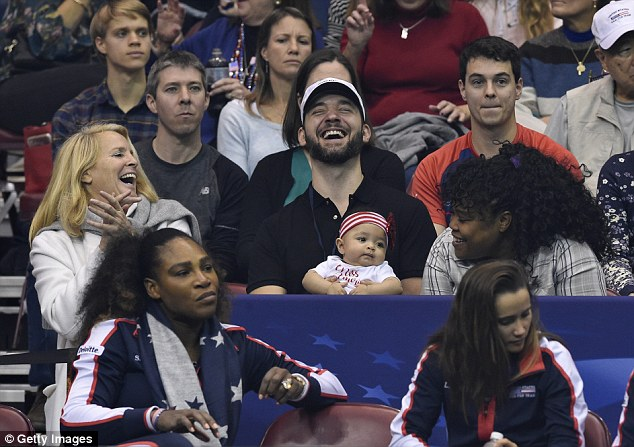 Dad duty: Alexis is pictured holding onto baby Olympia while mom is busy at the2018 Fed Cup inAsheville, North Carolina in February