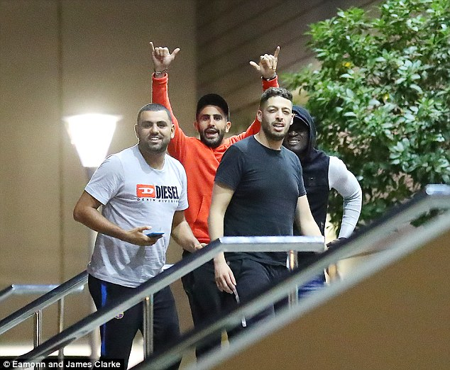 Mahrez, dressed in orange, is joined by a group of friends and spirits appear to be very high