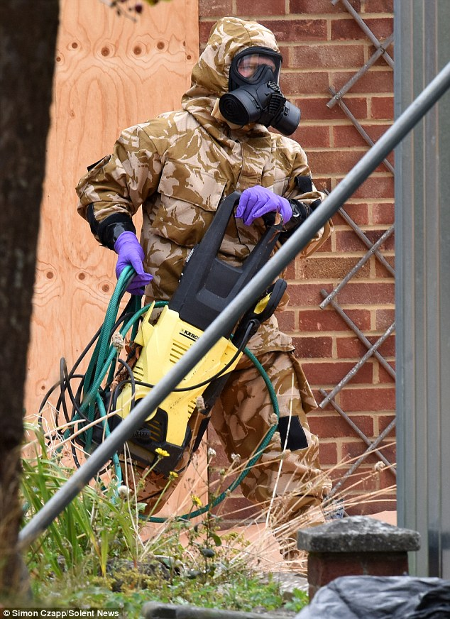Military personnel in protective clothing and gas masks decontaminate Sergei Skripal's home today, more than six months after he and his daughter were poisoned