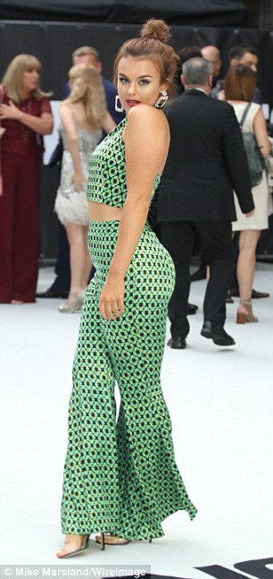 Sensational: Never one to shy away from a dramatic look, Tallia showcased her curves in the matching crop top and flared trousers with the green and black art-deco print