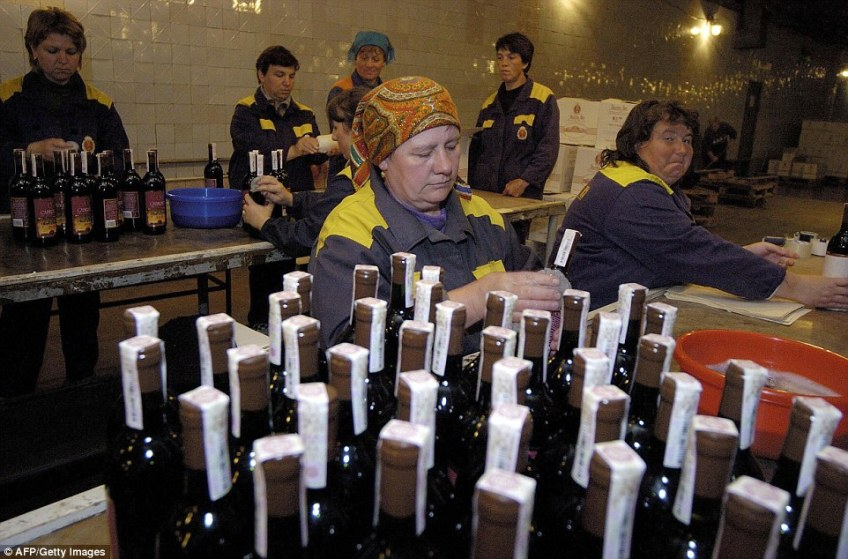 Workers put labels and authenticity stamps on the bottles of wine at Milestii Mici wineyard