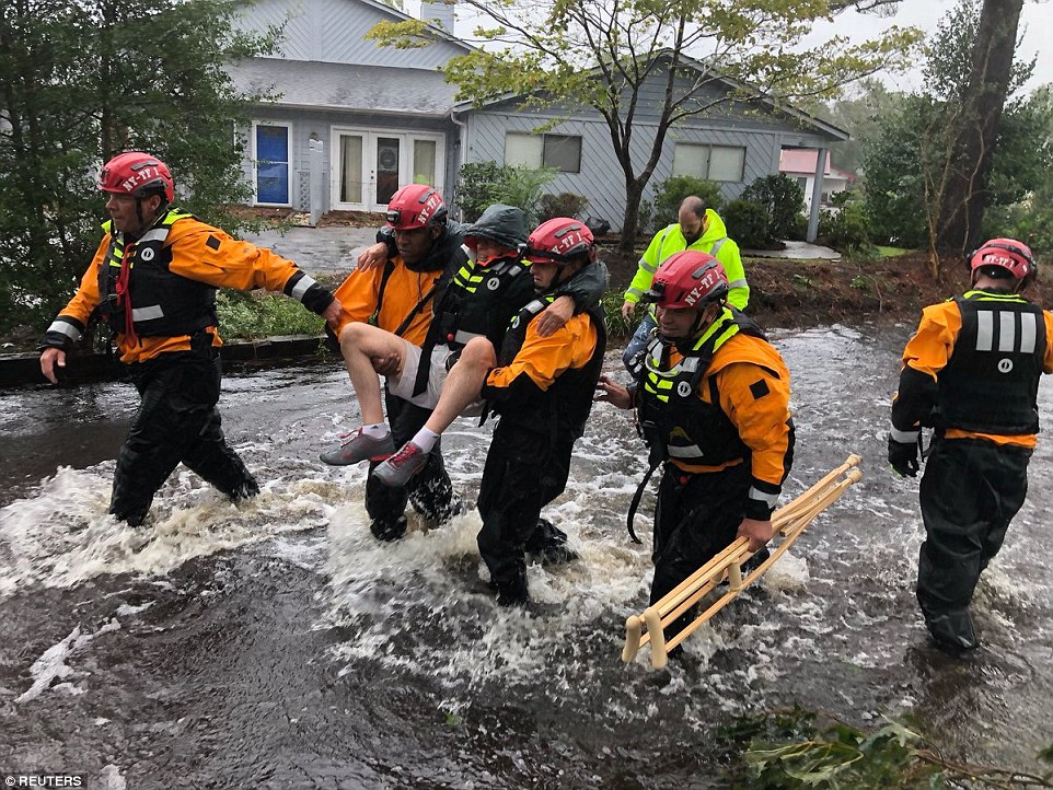 Firefighters use a boat to rescue three people from their flooded home during the Hurricane Florence in New Bern on Friday