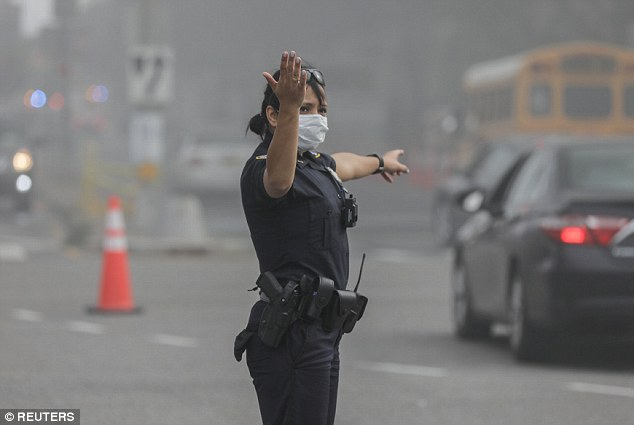A policewoman directs traffic during a seven-alarm fire while the public is urged to avoid the area