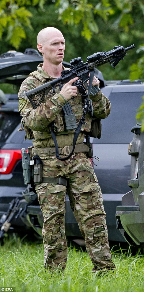 Armed police work at the scene of the shooting on Thursday morning