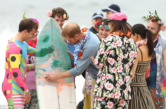 Chatting with another group of surfers, Harry said he had never waxed a board before, so he and Meghan both had a go