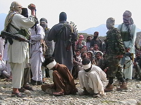 The two condemned men are surrounded by armed militants - one steadily filming the event on a video camera